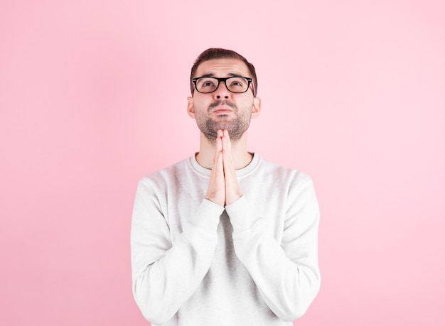 Мужчина в белом домашнем свитере загадывает желание на день рождения над розовой стеной.