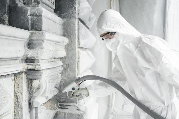 白い防護服を着た男が、サンドブラストマシンで土やコンクリートから石彫り彫刻をきれいにします。石の彫刻の修復。高圧下の砂の噴流。