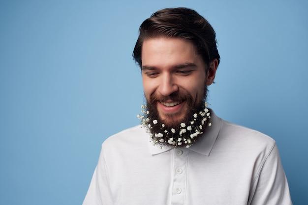 白いシャツを着た男がひげの理髪店の自然なスタイルで花を咲かせる