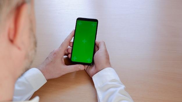 空白の緑色の画面で黒い携帯電話を保持している白いシャツの男