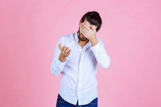 두통 때문에 그의 머리를 잡고 흰 셔츠에 남자.