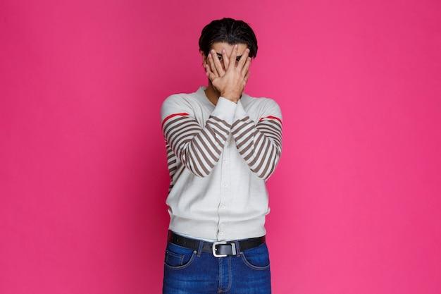 Мужчина в белой рубашке смотрит сквозь пальцы.