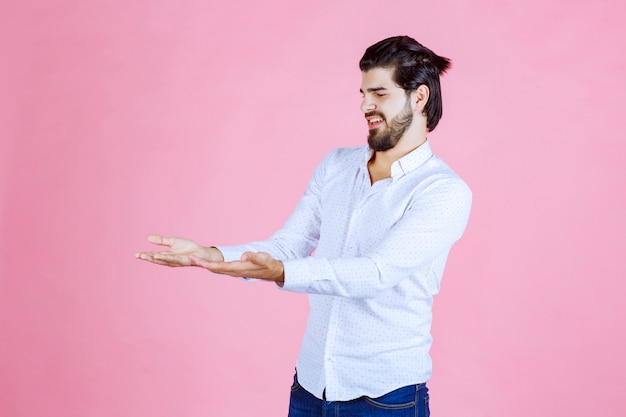 白いシャツを着た男性は混乱しているように見え、ハンドジェストを使用しながら自分自身を説明しようとしています。
