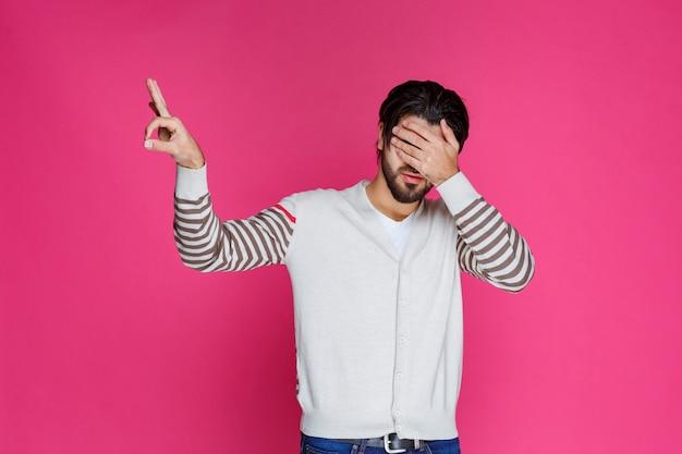 Человек в белой рубашке, делая знак круга пальцем.