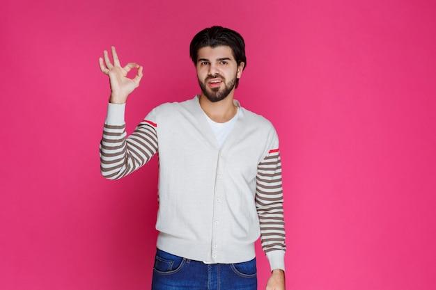 Человек в белой рубашке, делая знак руки полного удовлетворения или медитации.