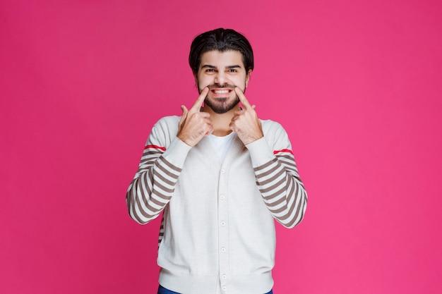 笑顔と陽気な顔にサインを作る白いシャツを着た男。