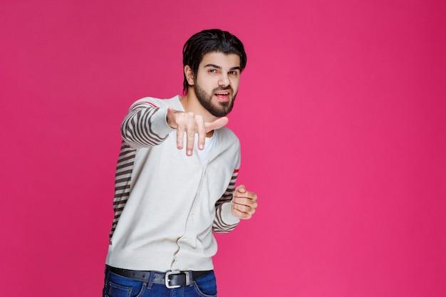 가입 엄지 손가락을 만드는 흰 셔츠에 남자.