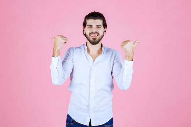 Человек в белой рубашке, указывая назад.