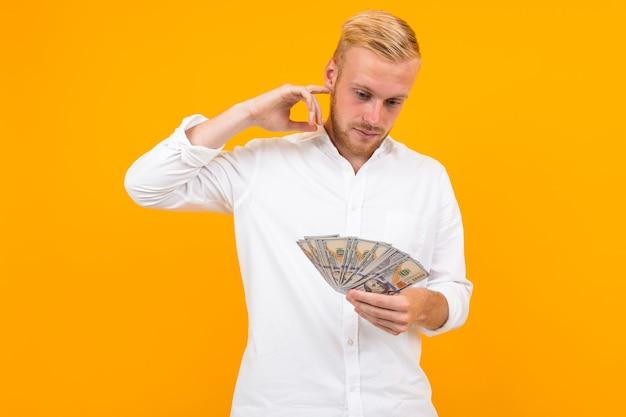 흰 셔츠를 입은 남자는 복사 공간이있는 노란색 배경에 번 돈을 쓸지 고민합니다.