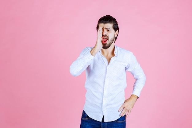 白いシャツを着た男が舌を出している。