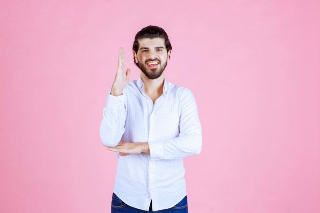Мужчина в белой рубашке поднимает руку, чтобы привлечь внимание или что-то показать.