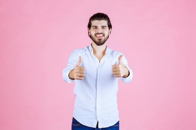 ポジティブな手のサインを示す白いシャツを着た男。