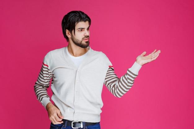 Мужчина в белой рубашке показывает что-то в руке.