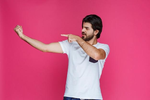 手に何かを見せている白いシャツを着た男。