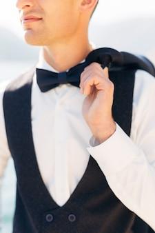 Мужчина в белой рубашке с галстуком-бабочкой держит перекинутую через плечо куртку