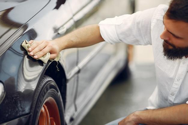 Человек в белой рубашке вытирает машину в автомойке