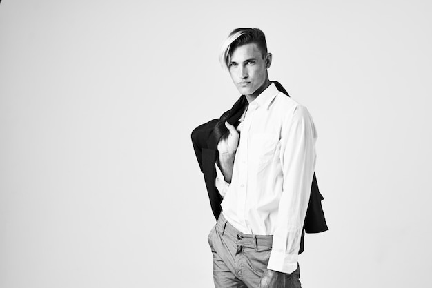 Мужчина в белой рубашке с курткой на плече модная прическа позирует на светлом фоне