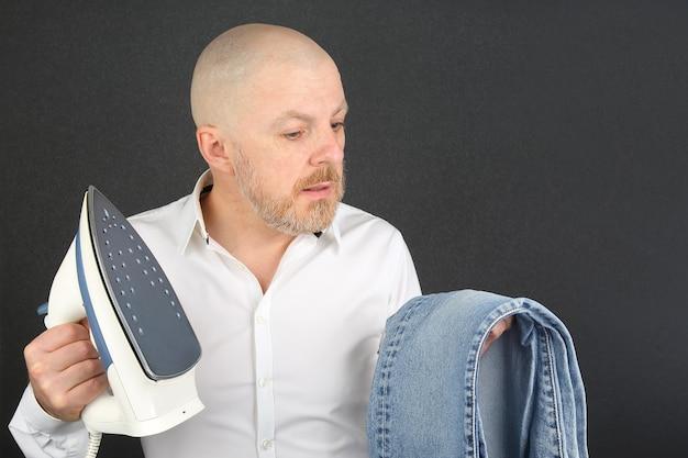アイロンフラットアイアンとジーンズを手にした白いシャツを着た男