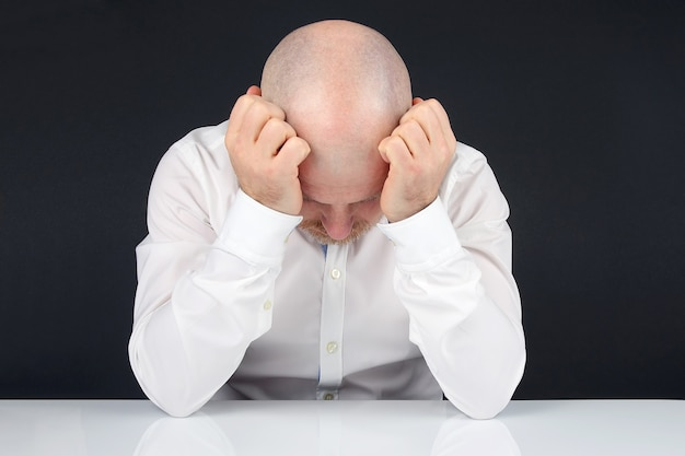 Человек в белой рубашке с поднятыми руками сидит за белым столом