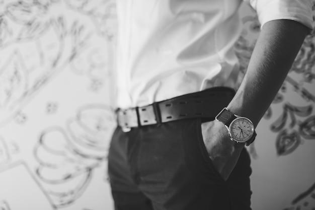 소매가 있는 흰색 셔츠를 입은 남자가 바지 주머니에 손을 넣었다