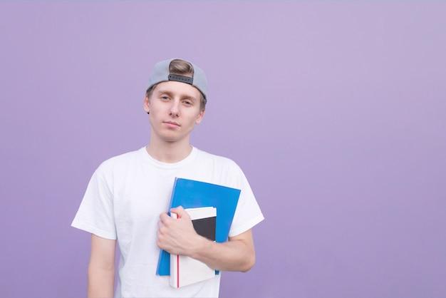 Человек в белой футболке стоит на фиолетовом фоне с книгами и тетрадями