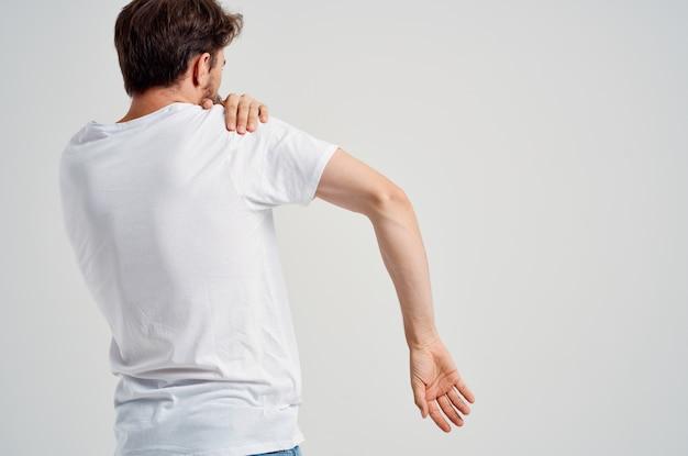 Человек в белой футболке стресс медицины боли в шее светлом фоне. фото высокого качества