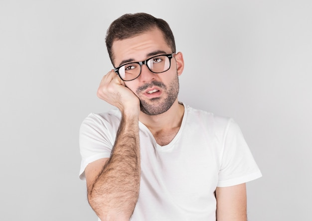 美しいあごひげを生やした白いtシャツを着た男性は横に疲れているように見えます。疲労、ストレス、過労の概念。