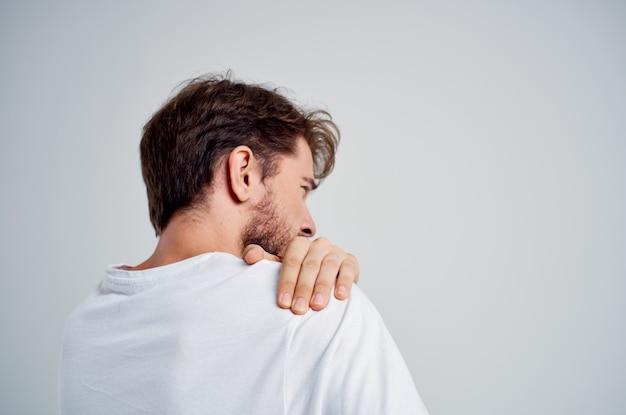 Мужчина в белой футболке снимает стресс, снимает боль в шее.