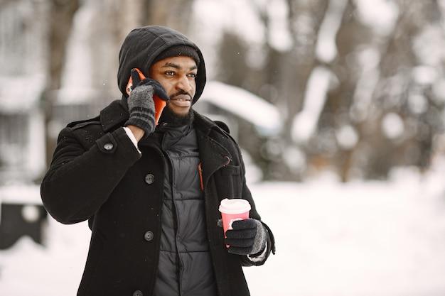 겨울 마을의 남자. 검은 코트를 입은 남자. 커피와 전화를 가진 남자입니다.