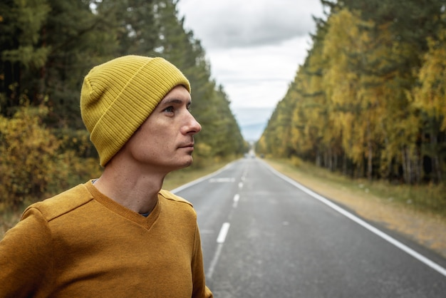노란 모자와 스웨터를 입은 남자가 아름다운 황금빛 숲을 따라 매끄러운 빈 아스팔트 길에 있습니다. 가을 분위기, 걷기, 야외 레크리에이션, 여행 및 하이킹의 개념