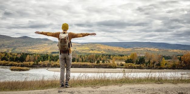 노란 모자를 쓰고 배낭을 메고 스웨터를 입은 남자가 강, 가을 황금빛 숲, 언덕 앞 양옆으로 팔을 뻗은 채 길에 서 있다