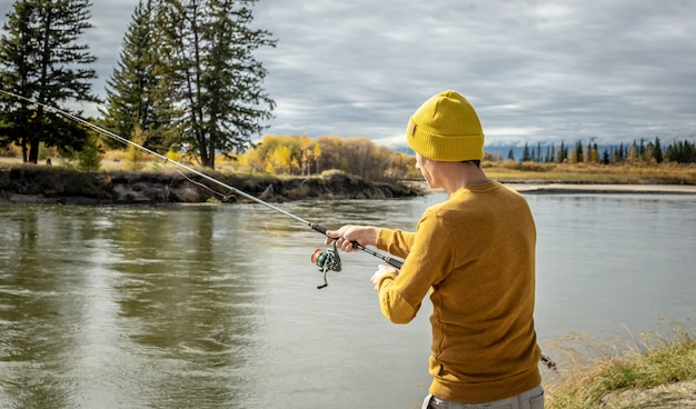노란 스웨터와 모자를 쓴 남자가 손에 물레를 들고 가을 숲의 강둑에서 낚시를 하고 있다
