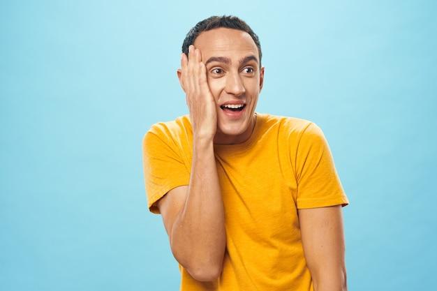 黄色のtシャツの感情の男は青い背景を見て驚いた
