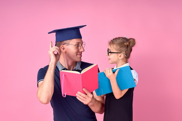 本を持っているアカデミックハットの男は、学校の制服を着たかわいいプレティーンの女の子と一緒に勉強します。父、娘はスタジオでピンクの背景に分離されました。家族の日親子のコンセプトが大好きです。