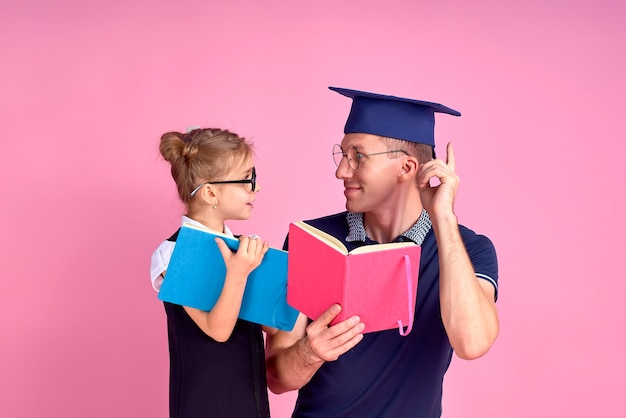 책을 들고 학술 모자 남자, 교복에 귀여운 초반 여자와 함께 공부