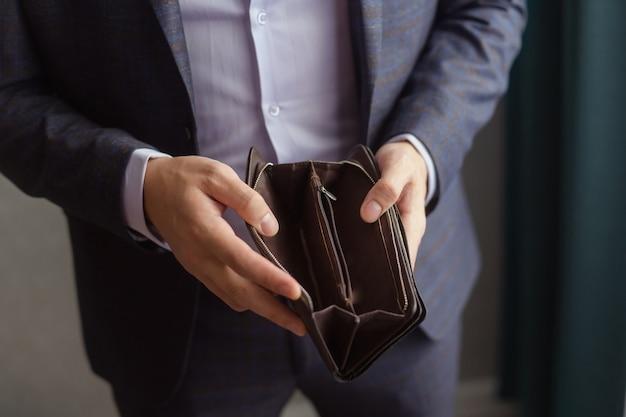 Мужчина в офисном костюме показывает пустой кошелек