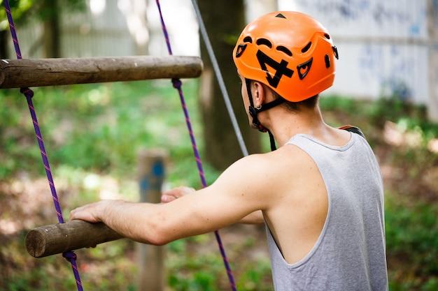 オレンジ色のヘルメットの男は、ロープのはしごに上がる