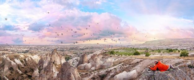 주황색 재킷을 입은 남자가 카파도키아 위로 아침 하늘에서 휴대폰으로 풍선 사진을 찍습니다. 파노라마. 괴레메, 터키