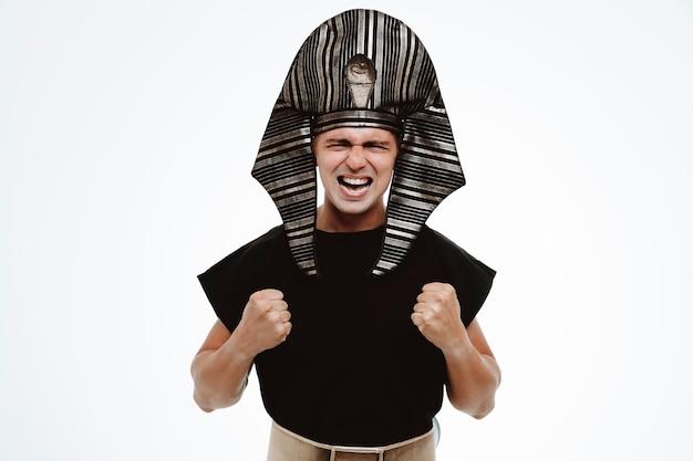 고대 이집트 의상을 입은 남자는 흰색에 화가 났고 좌절된 주먹을 꽉 쥐고 있다