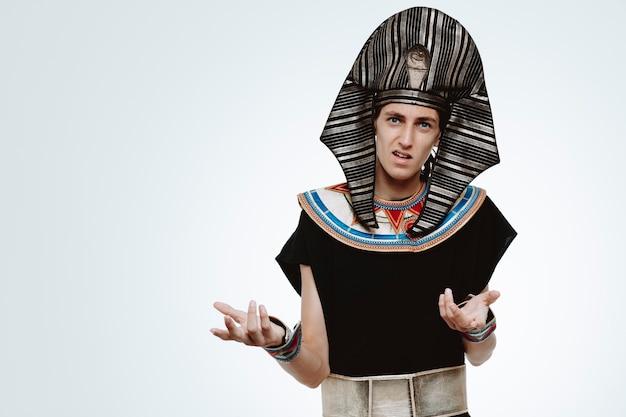 고대 이집트 의상을 입은 남자는 흰색에 분개하여 팔을 들고 혼란스럽고 불쾌했습니다.