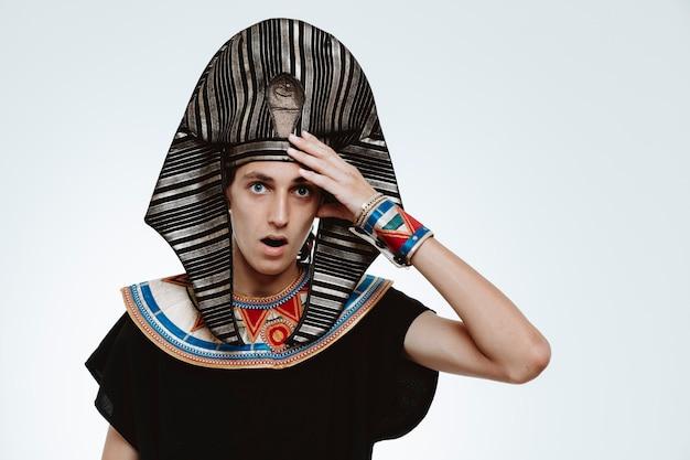 고대 이집트 의상을 입은 남자는 백인에 대한 실수로 머리에 손을 얹고 혼란스러워하고 걱정했다