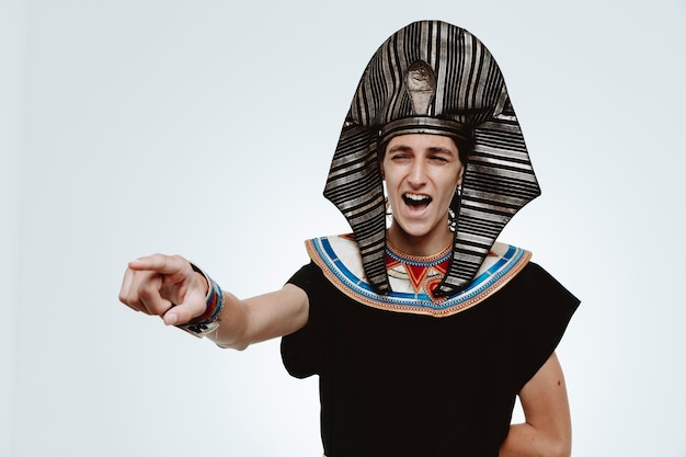 고대 이집트 의상을 입은 남자는 흰색에 있는 무언가를 검지 손가락으로 가리키며 미친 듯이 웃고 있습니다.