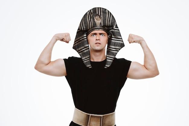 고대 이집트 의상을 입은 남자는 흰색에 승자처럼 주먹을 들고 흥분