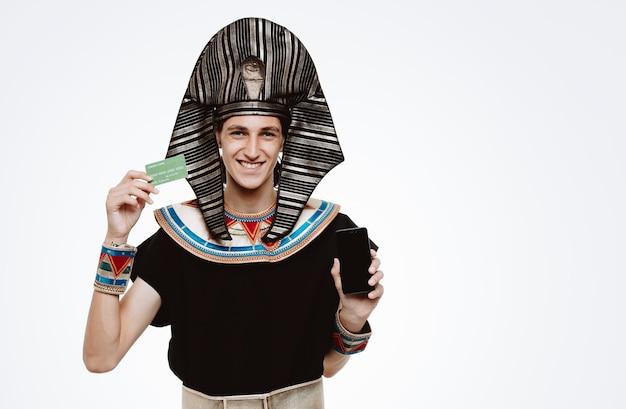 白で幸せで前向きな笑顔のクレジットカードを示すスマートフォンを保持している古代エジプトの衣装の男