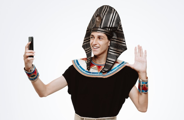 古代エジプトの衣装を着た男がスマートフォンを使用して自分撮りを撮って幸せで前向きな笑顔を白地に手で元気に振る