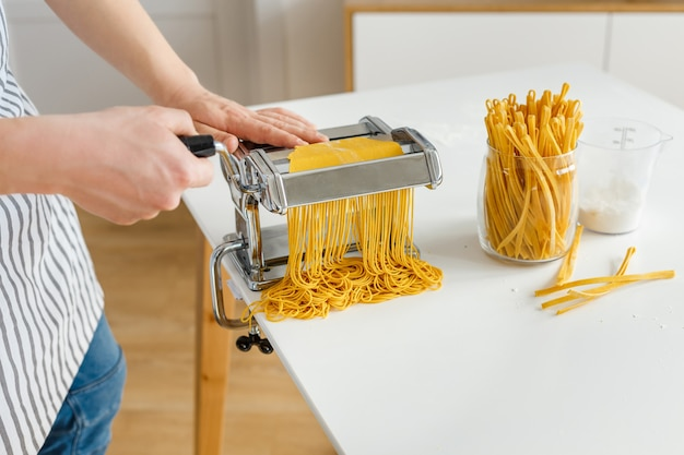 Мужчина в фартуке делает спагетти с ножом для лапши макароны крупным планом, готовят дома