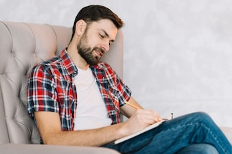 Man in armchair making notes