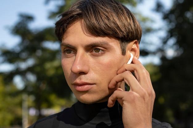 アスレチックウェアと屋外のイヤフォンの男