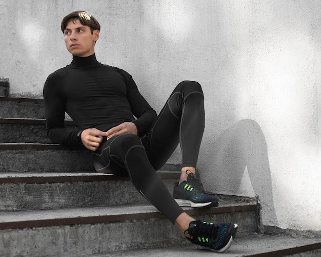 Человек в спортивной одежде позирует на лестнице на открытом воздухе