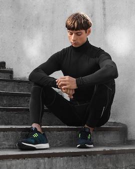 Человек в спортивной одежде позирует на лестнице снаружи